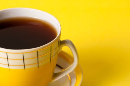 A yellow cup of tea or coffee without foam, close-up on a yellow background. Minimalistic composition with vintage subject and place for text on the right.