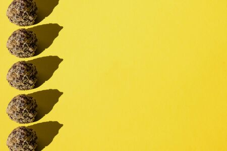 Pattern, chocolates on a yellow background, top view flat lay, copy space