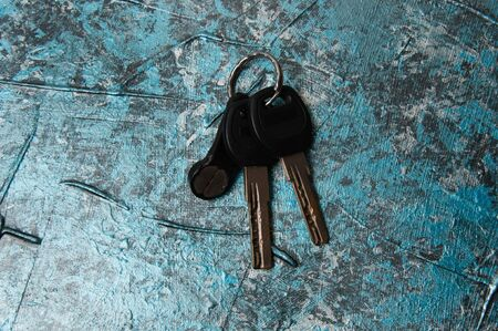 Keys to the house or flat concrete on blue background with copy space, view from the top. Resale purchase concept