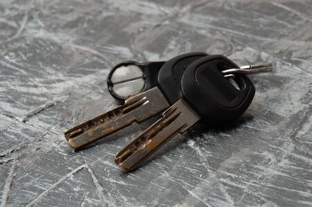 The keys to house or apartment on a gray concrete background with copy space, side view. The concept of buying a secondary in Europe housing