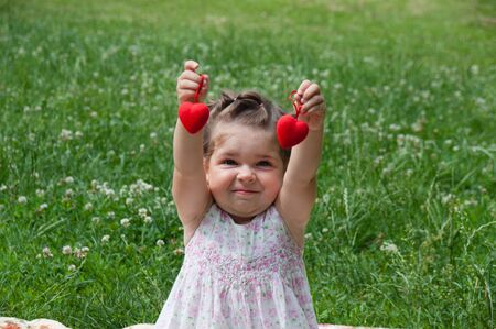Very beautiful baby girl sitting on a lawn in a park and plays cheerfully, holds red decorative hearts in her hands