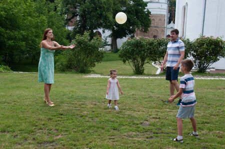 Happy parents play ball with children in the summer park.