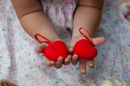 Two red hearts in the children's hands of little girl