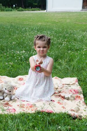 Very beautiful baby girl sitting on a lawn in a park and plays cheerfully, holds red alarm clock in her hands