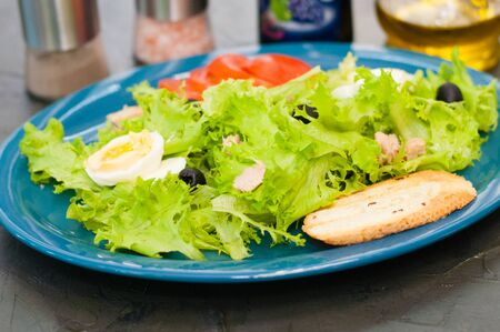 Salad with tuna, eggs, tomato, olives, spices and croutons, sauce or oil on a blue plate, close-up.