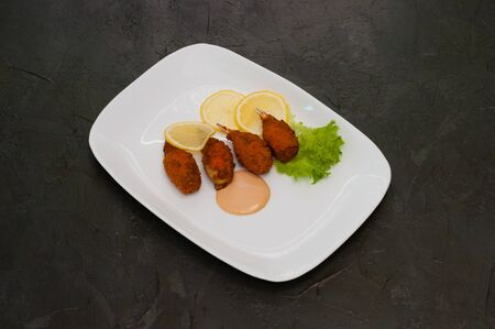 Crab claws fried in batter with lemon lettuce and tasty sweet and sour sauce. Festive dish of Italian cuisine