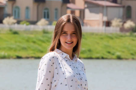 Smiling, pretty girl with long hair in white blouse on the bank of the city river, on the background of new houses