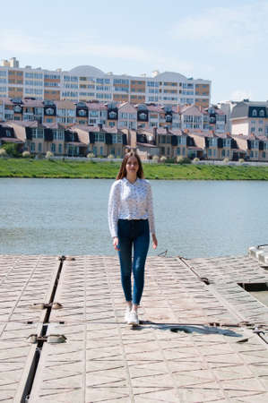Smiling, pretty girl with long hair in a white blouse goes on the banks of the river city against the backdrop of new homes