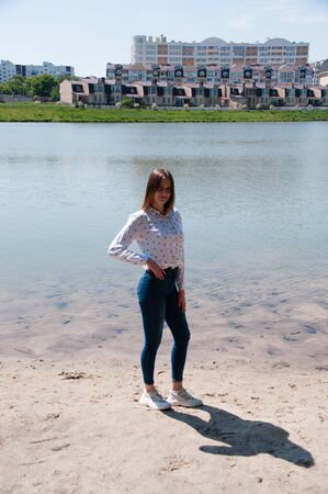 Beautiful girl in a white shirt and jeans on the river bank in the city of Chernihiv against the background of new houses