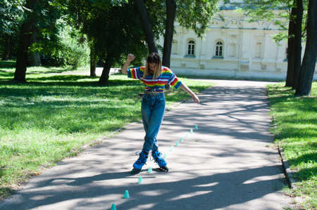 Beautiful girl having fun roller-skating in the park in the summer, vyponyaet tricks and toured chips.