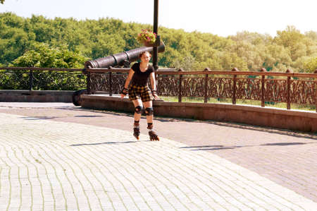 Beautiful, athletic and woman rides rollerblading in the park
