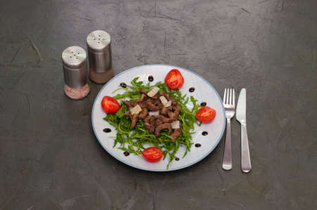 Tasty and juicy grilled meat with arugula, cheese, tomato sauce and spices on a dark gray concrete background, top view