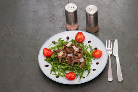 Tasty and juicy grilled meat with arugula, cheese tomato sauce and spices on a gray concrete background Banque d'images