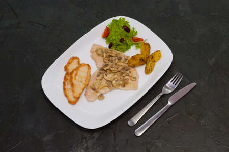 Stewed mushrooms with fish fillet, salad, fried potatoes and croutons on a warm gray background. Tasty traditional italian food