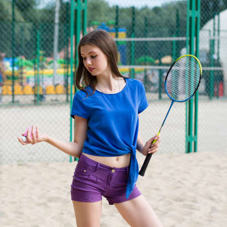 Young pretty woman having fun on the beach playing badminton Stock Photo