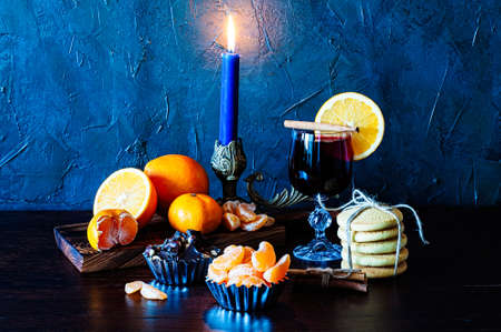 Christmas time, winter, mulled wine in a glass, cinnamon, orange and mandarin, cookies and chocolate, a candle in a candlestick.