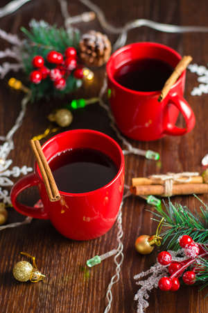 Delicious mulled wine with cinnamon in red cups. Concept waiting for christmas, top view, vertical format.