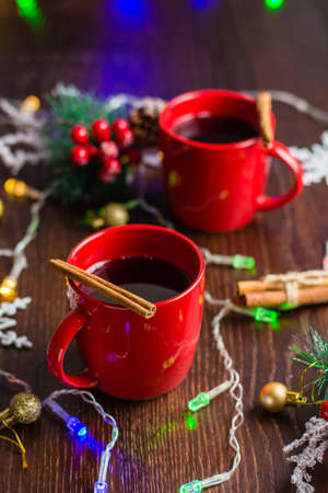 Delicious mulled wine with cinnamon in red cups. Concept waiting for christmas, top view, vertical format