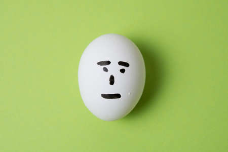 An egg with an indifferent face, on a green background with copy space.