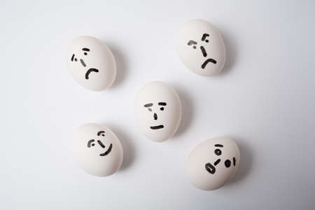 Eggs on white background, with different emotions on their faces 版權商用圖片