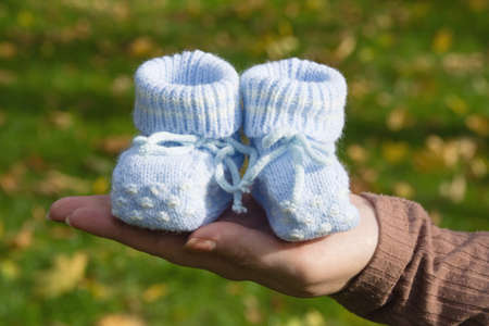 Booties for a newborn close-up in mothers hands copy space