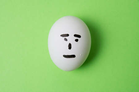 An egg with an indifferent emotion on the face, on a green background copy space Standard-Bild