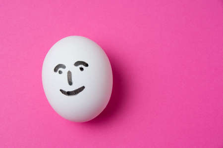 Egg with a happy face on a pink background with copy space.