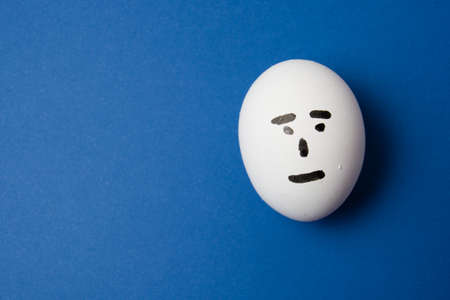 Egg with an indifferent face, on blue background with copy space.