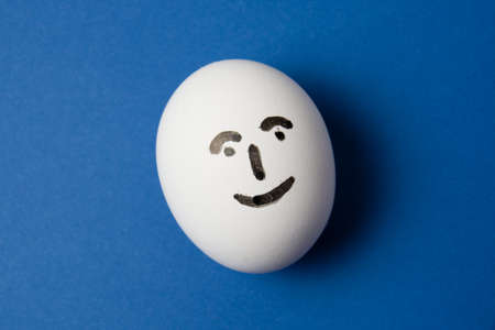Egg with a happy face on a blue background with copy space. Standard-Bild