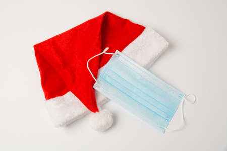 Santa hat and medical mask on white background close up with copy space.