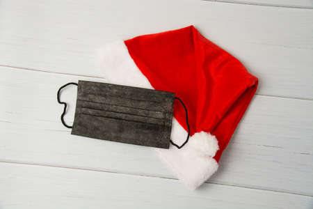 Santa claus hat and black medical mask on light wooden table close up copy space.