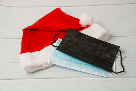 Santa claus hat and medical masks on light wooden table close up copy space.
