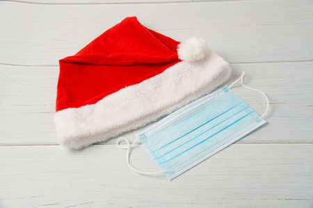 Santa claus hat and medical mask on a light wooden table close up copy space.