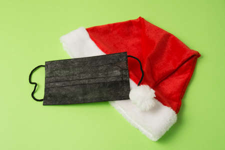 Santa claus hat and black mask on green background close up copy space.