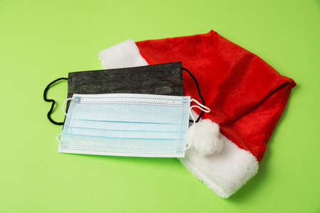 Santa claus hat and medical masks on green background close up copy space.
