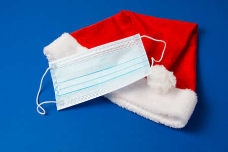 Santa claus hat and mask on blue background close up copy space.