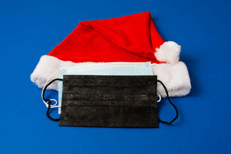 Santa claus hat and medical masks on blue background close up copy space. Standard-Bild