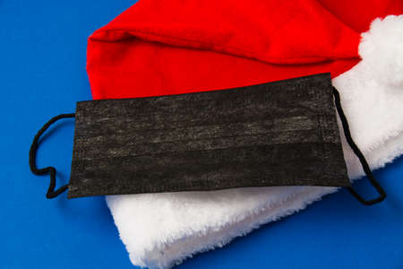 Santa claus hat and black mask on blue background close up copy space. Standard-Bild