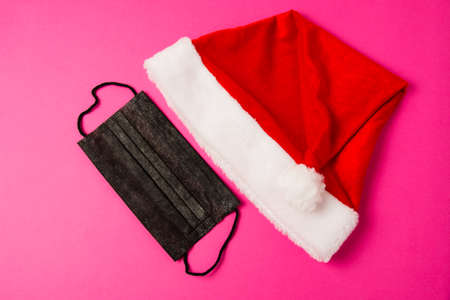 Santa claus hat and black mask on pink background close up copy space