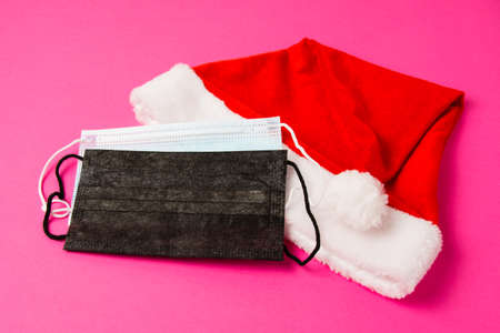 Santa claus hat and medical masks on bright pink background close up copy space.