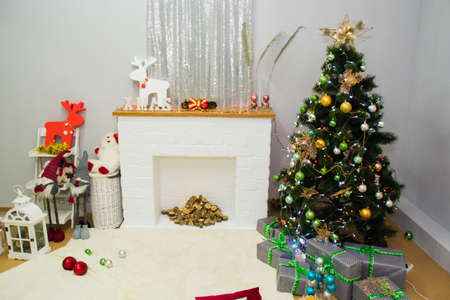 New Year's interior, a beautiful photo zone with a Christmas tree, fireplace and gifts. Standard-Bild