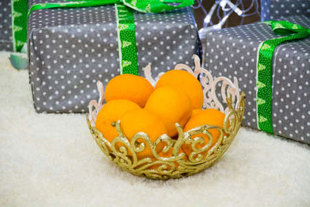 Vase with tangerines under a christmas tree, copy space.