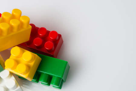 Many multicolored cubes of children's constructor blocks on a white background top view with copy space. Concept building plans and goals. Standard-Bild