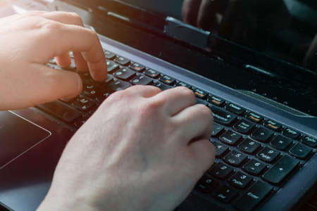 Hands and laptop keyboard close-up, soft focus. A man or woman uses a laptop to study online, work, search for information on the Internet. Warm morning sun