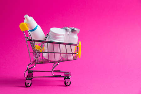 Medicines, drops in a metal trolley for a buyer from a supermarket on a pink paper background. The concept of medicine and the cost of treatment Standard-Bild