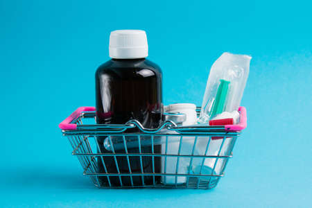 Medicines in a shopping cart for a shopper from a supermarket on a blue paper background. The concept of medicine and the cost of treatment