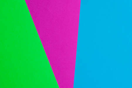 Bright paper background consisting of three colors: pink, green and blue.