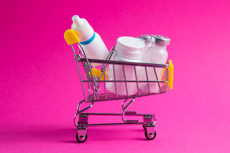Medicines, drops in a metal trolley for a buyer from a supermarket on a pink paper background. The concept of medicine and the cost of treatment. Standard-Bild