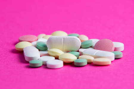 Many multicolored vitamins and pills on a pink background copy space, close-up