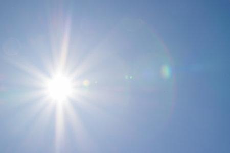 Clear blue sky, sun, beautiful sunbeams and glare